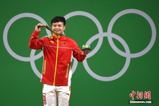 图为龙清泉展示奥运金牌。中新网记者 富田 摄