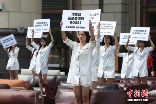 """资料图:上海街头,一场名为""""孤独沙发""""的行为艺术上演,40位孤独的女性集体站上沙发,呼吁""""8.16不加班""""。 中新社记者 张亨伟 摄"""