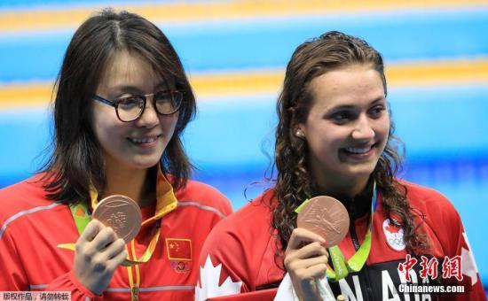 当地时间8月8日,在2016里约奥运女子100米仰泳决赛上,中国选手傅园慧以58秒76夺得铜牌。图为傅园慧(左)登台领奖。