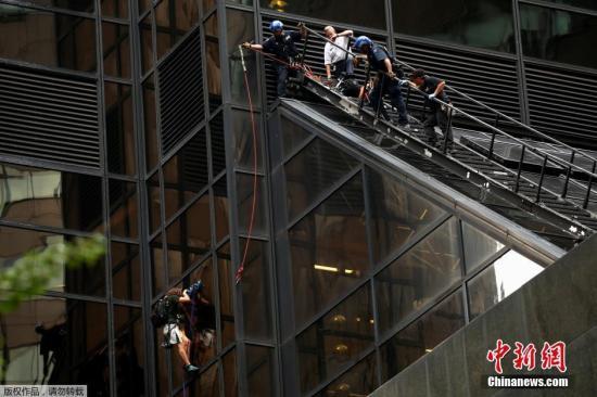 资料图:当地时间2016年8月10日,美国纽约,一名男子使用吸盘攀爬特朗普大楼,警方通过21楼的窗户将其带离。