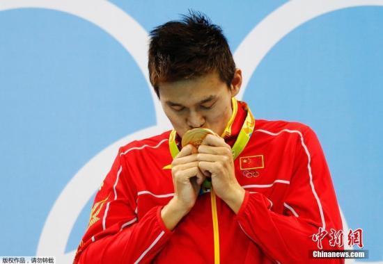 图为孙杨在200米自由泳夺冠后亲吻金牌。