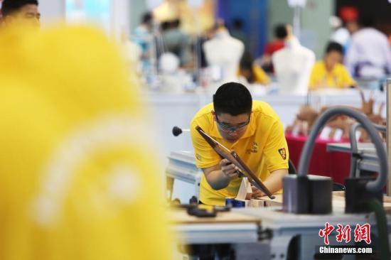 资料图:参加世界技能大赛的选手正在进行精细木工项目竞技。 中新社记者 张亨伟 摄