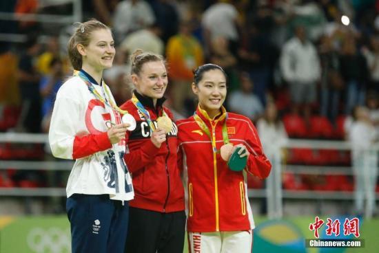 本地时刻8月12日,2016里约奥运会男子蹦床,国家选手李丹以55.885分取得铜牌。图为李丹(右)与冠亚军合影。中新网记者 杜洋 摄