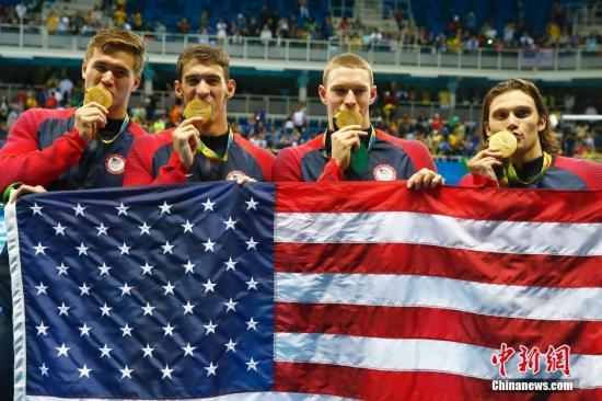 8月13日,在里约奥运会游泳赛场最后一天的比赛中,菲尔普斯领衔的美国队在男子4X100米混合泳接力决赛中,获得冠军,这块金牌成为菲尔普斯的奥运会第23金,完美收官。中国队因为犯规被取消成绩。图为美国队集体吻金牌庆祝。记者 富田 摄