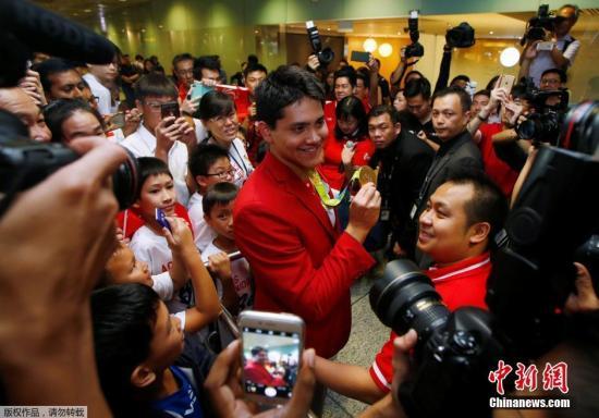 资料图:当地时间8月14日,新加坡游泳运动员约瑟林在奥运会获得男子百米蝶泳金牌后,回到新加坡。在樟宜机场他的粉丝和教练以及众多记者把现场围的水泄不通。