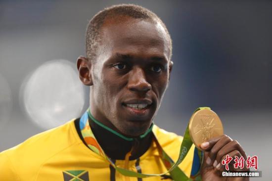 当地时间8月15日,里约奥运会男子100米颁奖仪式在里约奥林匹克体育场举行。图为博尔特展示金牌。记者 盛佳鹏 摄