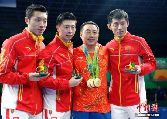 2016里约奥运男子乒乓球团体赛决赛,中国队最终以总比分3:1的成绩战胜日本队获得冠军。图为许昕(左一)、马龙(左二)、刘国梁(右二)、张继科在领奖台上合影。<a target='_blank' href='http://www.chinanews.com/' >中新网</a>记者 盛佳鹏 摄