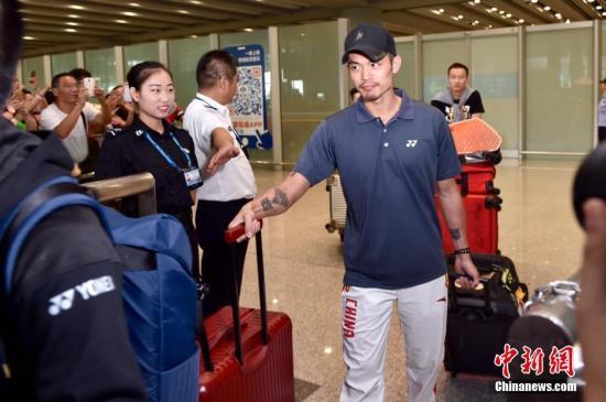 8月22日,中国奥运羽毛球队抵达首都机场,被早已等候在现场的球迷层层包围。图为林丹走出机场,受到好友鲍春来的热情迎接。记者 金硕 摄