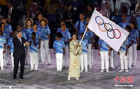 资料图:手握奥林匹克五环旗的日本东京都知事小池百合子。