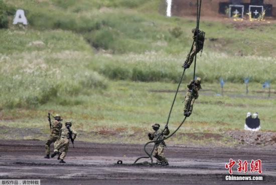 当地时间8月25日,日本御殿场市东富士演习场,日本陆上自卫队举行年度富士综合火力演习。图为日本自卫队队员进行机降演示。