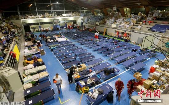 各方担心,伤亡数字还会进一步攀升。图为当地一处体育馆被当做临时避难所,馆内堆满了生活物资和简易床。