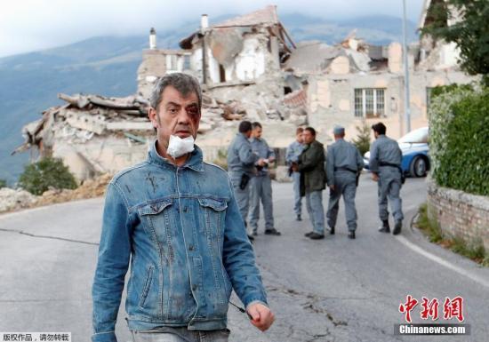 8月25日,一名伤者走在倒塌的房屋前。