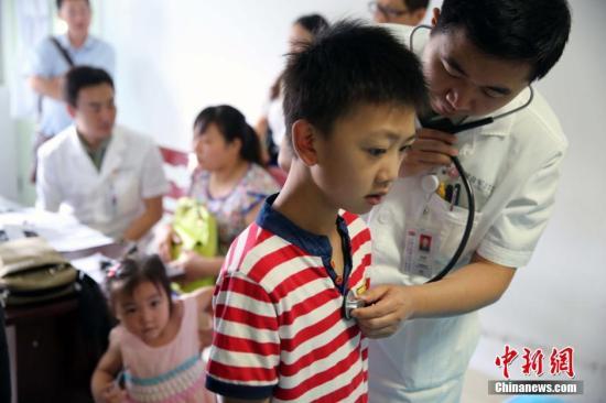 资料图; 医生在给儿童做检查。