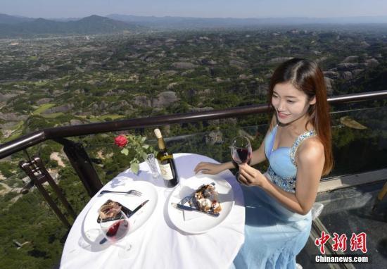 资料图:游人在悬崖边吃甜品、品红酒,体验高空感受。 中新社记者 杨华峰 摄