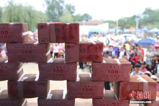 """甘肃一村庄堆百万元""""钱山"""",给80余农户分红。图为领到分红村民一起合影。 刘玉桃 摄"""