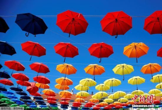 资料图片:奥地利维也纳,杜诺广场挂满彩色雨伞,映衬着蓝天白云,美丽如画。