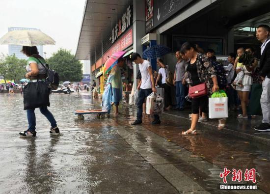 资料图:重庆迎来降雨降温天气,市民冒雨淌水前行。 周毅 摄
