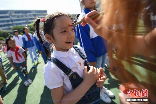"""9月5日,山西太原迎泽区第二实验小学举行开学仪式,老师们为新入学的小学生们点朱砂,行""""开笔礼""""。图为老师们为新入学的小学生们点朱砂。武俊杰 摄"""