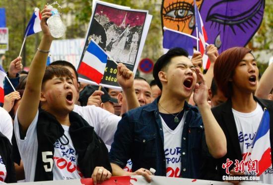 """法国华社9月4日在巴黎市中心举行声势浩大的集会游行,悼念遇暴力抢劫被殴致死的旅法侨胞张朝林。来自法国社会各界的数万华侨华人共同发出""""反暴力,要安全""""的强烈呼声。图为参加游行的华人奋力发声。 中新社记者 龙剑武 摄"""