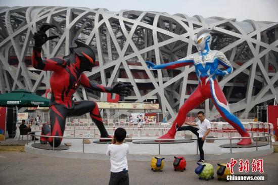 """9月4日,巨型""""奥特曼""""现身北京国家体育场附近,吸引了游客的关注。 <a target='_blank' href='http://soyew.com/'>中新社</a>记者 刘关关 摄"""