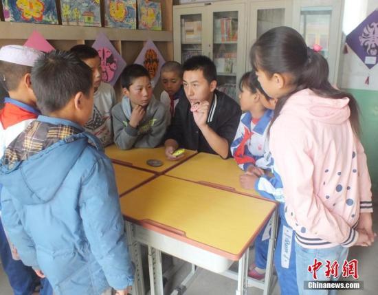 资料图:甘肃一乡村小学的教师为学生上课。郭红 摄