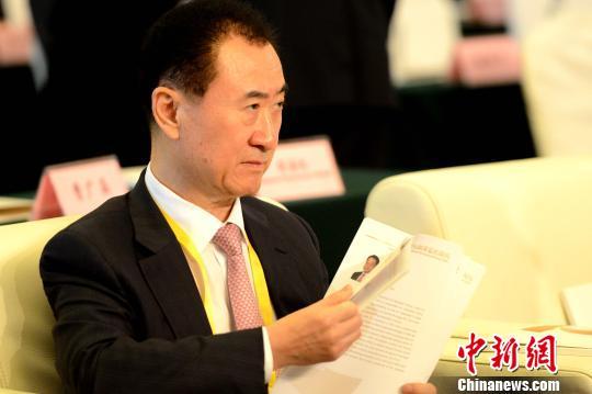 王健林在论坛现场看材料。 王东明 摄