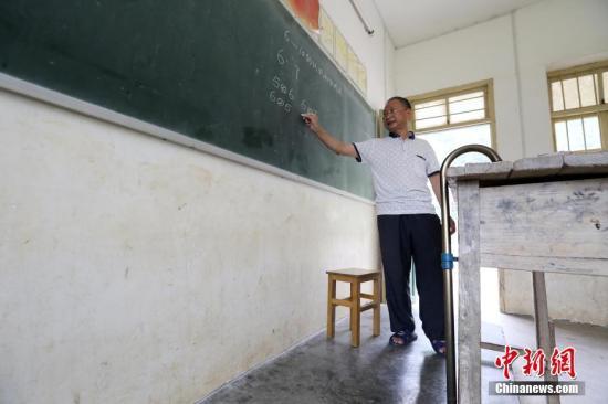 资料图:在广西柳州市融安县东起乡,教师李朝文拄着拐杖一直坚守在三尺讲台上,至今已经第30个年头。