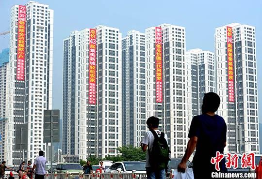 资料图:市民从正在销售的楼盘旁经过。<a target='_blank' href='http://www.chinanews.com/'>中新社</a>记者 张斌 摄