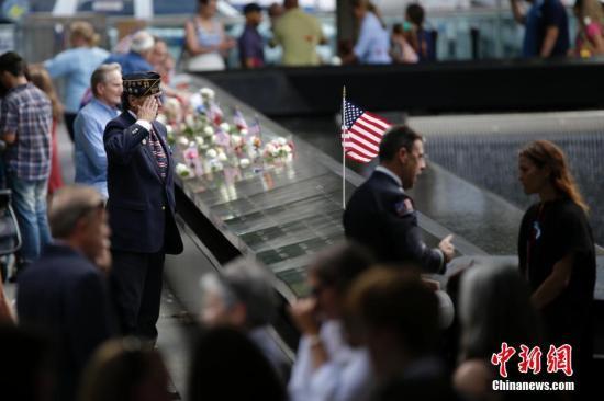 """当地时间9月11日,民众在纽约世贸遗址前哀思。当日,""""911""""15周年纪念活动在美国纽约911纪念公园举行。 记者 廖攀 摄"""
