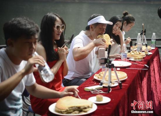 9月12日,湖南大胃王潘一中在长沙石燕湖接受了四位网络女主播及游客的挑战。 杨华峰 摄