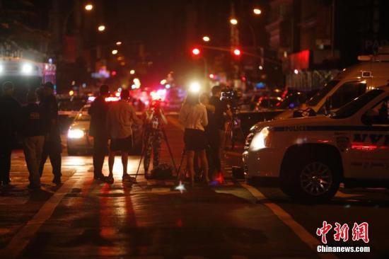 """当地时间9月17日,纽约曼哈顿切尔西街区,记者在警戒区外采访。当晚,纽约曼哈顿切尔西街区的爆炸已造成29人受伤,一人伤势较重,但无生命危险。初步调查显示,这是一起""""蓄意行为"""",但目前尚无证据显示爆炸与恐怖袭击有关。<a target='_blank' href='http://www.chinanews.com/'>中新社</a>记者 廖攀 摄"""