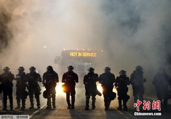"""本地时刻9月20日晚,美国北卡罗来纳州夏洛特市暴发黑人暴力请愿流动,反对差人枪杀一位黑人女子。抵触招致12名差人受伤、多辆警车被破坏。本地警方称,一些""""鼓动者""""参加反对流动后,发作了暴力举动。图为防暴差人在现场。"""