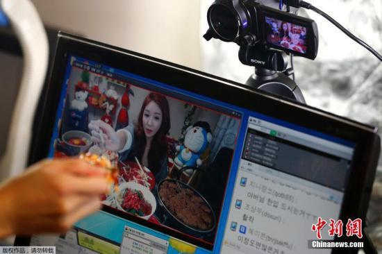 资料图:韩国仁川,Park Seo-yeon在公寓中视频直播自己吃饭。