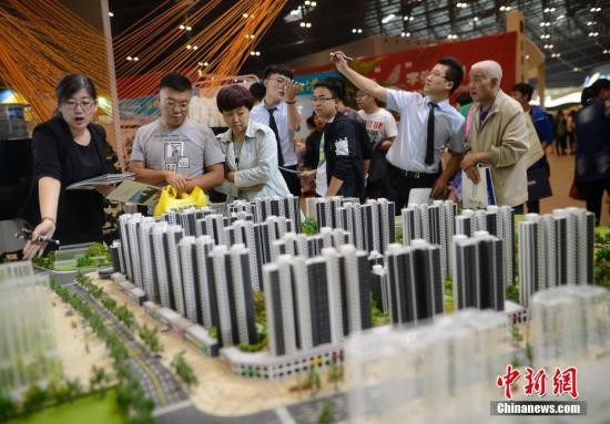 资料图 中国某地售楼员为民众推荐商品房户型。 韦亮 摄