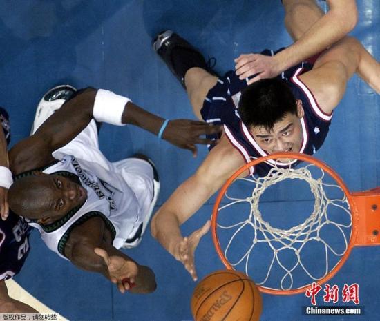 2003年2月4日,NBA聯賽,美國明尼蘇達森林狼的凱文·加內特(左)與火箭隊的姚明正在爭搶籃板球。