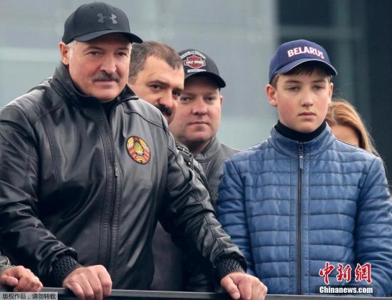 资料图:白俄罗斯总统卢卡申科身着皮衣,带着自己的小儿子尼古拉参加摩托车巡游活动。