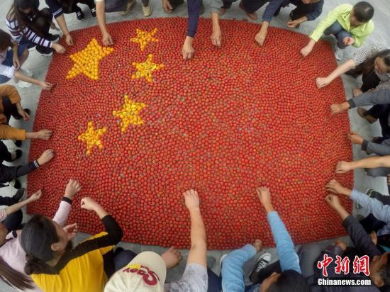 9月30日,中华人民共和国迎来67周年华诞,河南济源黄河三峡,生长在母亲河畔的民众,在黄河岸边用熟透的红果山楂和金黄的柿子拼成五星红旗,以他们独特的方式表达对共和国的热爱之情。<a target='_blank' href='http://www.chinanews.com/'>中新社</a>记者 王中举 摄