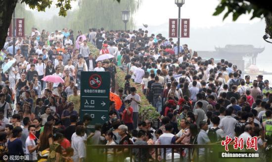 10月1日,国庆长假首日,杭州西湖断桥景区人潮涌动。吴煌 摄 图片来源:CFP视觉中国