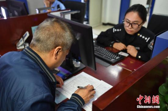 """10月1日,民众在北京市西城区厂桥派出所填写《北京居住证》申请办理的相关材料。当日起,《北京市实施〈居住证暂行条例〉办法》正式施行,北京346个户籍派出所正式受理来京人员申领《北京市居住证》,这也意味着""""暂住证""""将转变为""""居住证""""。记者 崔楠 摄"""