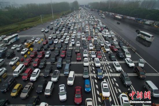 10月1日,大批车辆缓慢经过南京长江二桥高速公路收费站。当日是中国国庆长假首日,大批市民或探亲访友或出游,多地出现出行高峰。中新社记者 泱波 摄