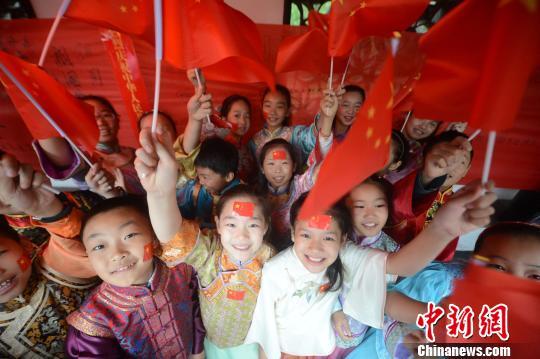 """资料图:扬州小朋友""""唱国歌送祝福""""喜迎祖国华诞。孟德龙 摄"""