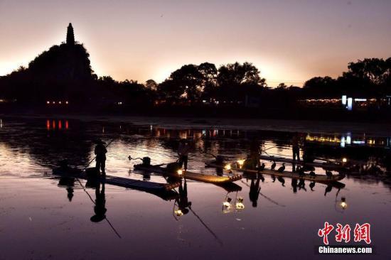 """10月3日,广西桂林穿山公园一年一度的""""塔山渔火""""活动火热上演,吸引了上千名游客和摄影爱好者。漓江渔火,原是漓江上渔家人的一种传统渔事活动,每当夜幕降临,渔民们便乘上竹筏,点上火把,排头挂着汽灯,带上几只鸬鹚,撒网捕鱼。穿山公园将其引入塔山脚下小东江畔,演绎为""""塔山渔火"""" 经过多年打造""""塔山渔火""""已成为桂林旅游响亮品牌。 唐梦宪 摄"""