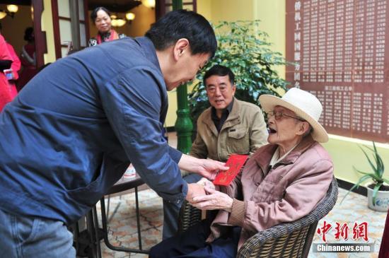 资料图 工作人员向归国华侨送上节日问候。 记者 刘冉阳 摄
