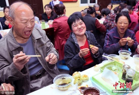 资料图:西安老人家们围桌而坐,几百人一起吃包子、吃馄饨、聊家常。