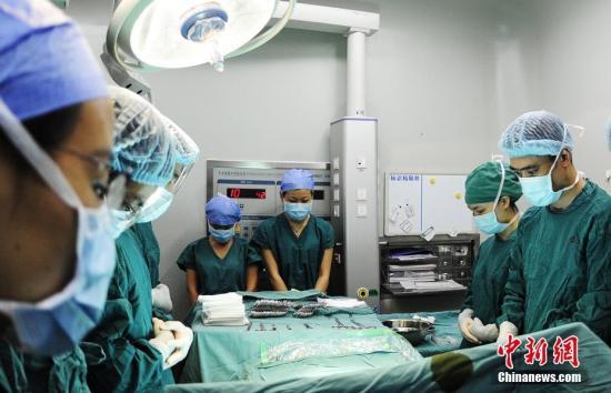 资料图:医务人员在术前为逝去的器官捐献者默哀。安源 摄