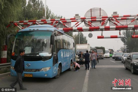 资料图:旅游大巴被限高杆卡住引拥堵。高立萌 摄 图片来源:视觉中国