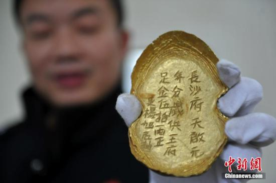 """警方展示追回的一级文物五十两金锭,上面刻有""""长沙府天启元年足金五十两等字样。 <a target='_blank' href='http://www.chinanews.com/'>中新社</a>记者 刘忠俊 摄"""