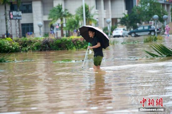 """资料图:台风""""莎莉嘉""""在海南登陆,琼海市民涉险通过积水路段。 骆云飞 摄"""