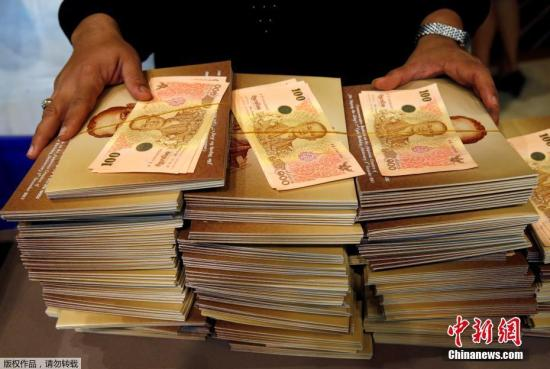 当地时间10月18日,泰国曼谷民众排队购买以国王普密蓬为主题的100泰铢纪念钞。