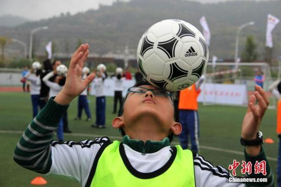 """10月23日,作为""""校园足球新长征""""活动的主要内容之一,一堂""""校园足球公开课""""在延安实验小学展开,几十名来自当地的学生在教练的指导下,感受快乐足球。""""校园足球新长征""""是由全国青少年校园足球工作领导小组办公室主办,各省市青少年校园足球工作领导小组办公室承办的一项大型宣传推广活动,自今年5月在北京市八一学校启动以来,已在全国20个省(区、市)开展了相关活动。张一辰 摄"""